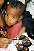Child in mother's arms as she works on an embroidery on the NACOEJ Compound for Ethiopian Jews in Addis Ababa, Ethiopia