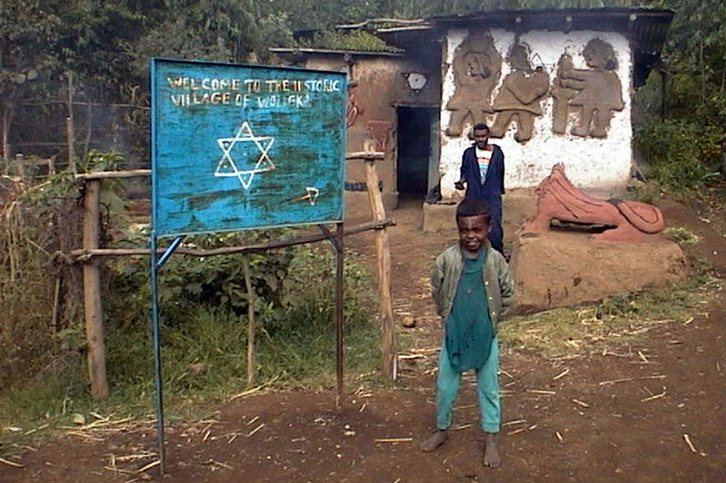 """Sign at welcomes visitors to the formerly Jewish village of Wolleka, Gondar, Ethiopia (the building seen in the background with the designs on the wall was built by Christian squaters as was the lion statue and the sign declaring """"Welcome to the Historic Village of Wolleka"""" which was not there when the village was Jewish. While the raised fresco on the new white building were not there when Wolleka was Jewish, there was a fine raised fresco on a grass roofed house across the street when Jews lived left the village of Wolleka in 1990."""