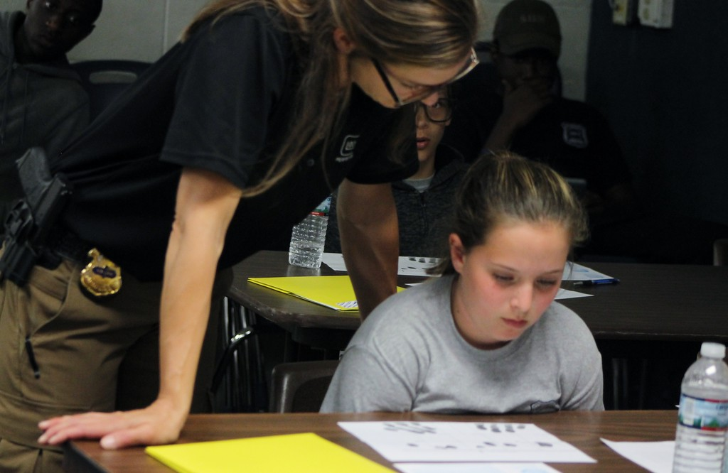 . Kristi Garabrandt - The News-Herald Euclid Det. Jen Kroczak instructs Junior Police Academy Cadets Kaelynn McCauley and Chase Clark on how to take fingerprints.