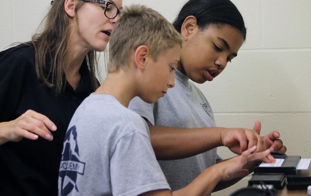 . Kristi Garabrandt - The News-Herald Euclid Det. Jen Kroczak instructs Junior Police Academy Cadets Kaelynn McCauley and Chase Clark on how to take fingerprints.