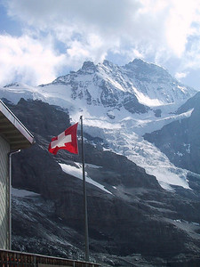 Swiss flag in front of Monch, Swiss Alps.