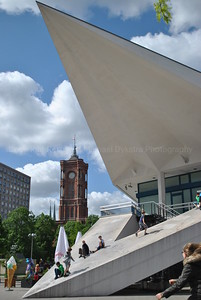 Traditional church steeply captured by the base of Fernsehturm TV tower