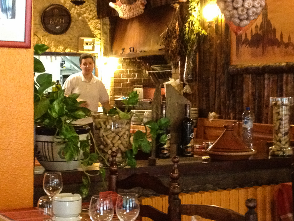 Owner tending the grill at l'Hort de Casa restaurant in Erts. Counter with plants and table with glasses in foreground.