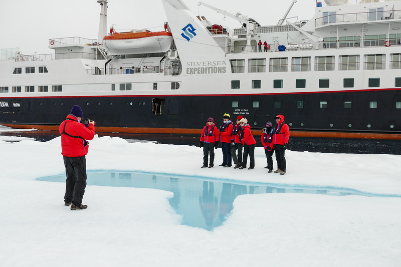 man in red coat taking photo of group on ice behind cruise ship