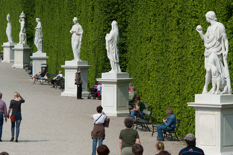 Tourists near row of sculptures in Schonbrunn Garden - Vienna, Austria