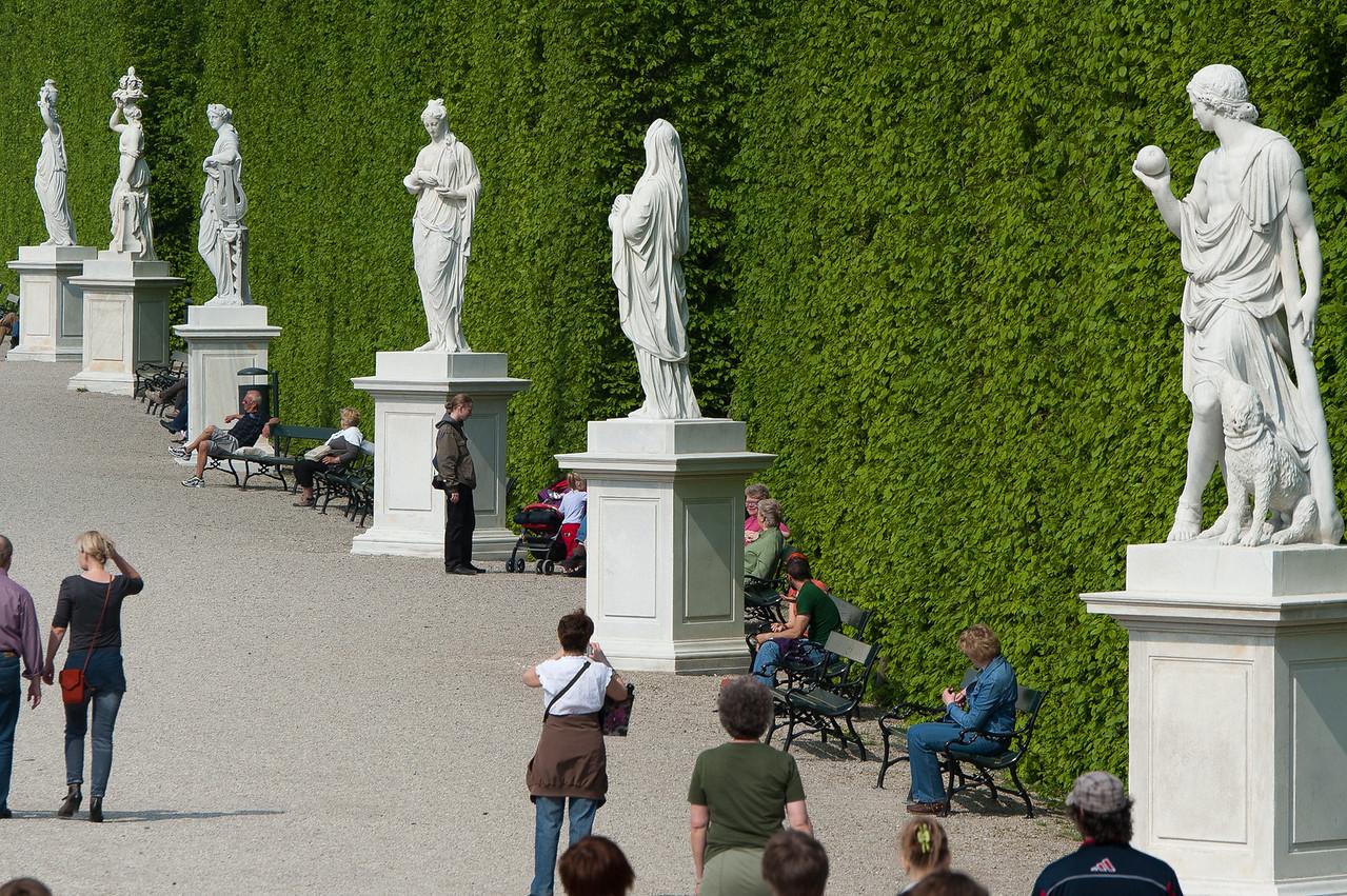 Tourists near row of sculptures in Schonbrunn Garden - Vienna, Austria