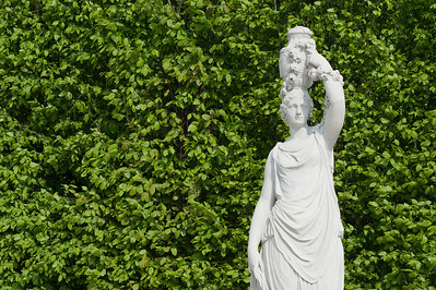Statue against flora in Schonbrunn Palace - Vienna, Austria