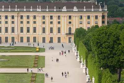 Tourists walking along a row of sculptures in Schonbrunn Palace - Vienna, Austria