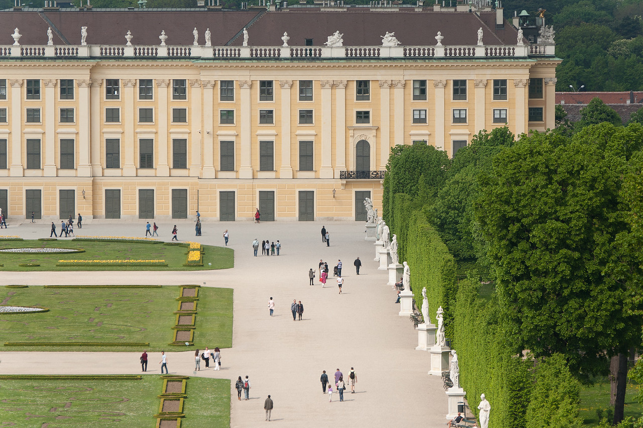Tourists walking along a row of sculptures in Schonbrunn Palace - Vienna, Austria