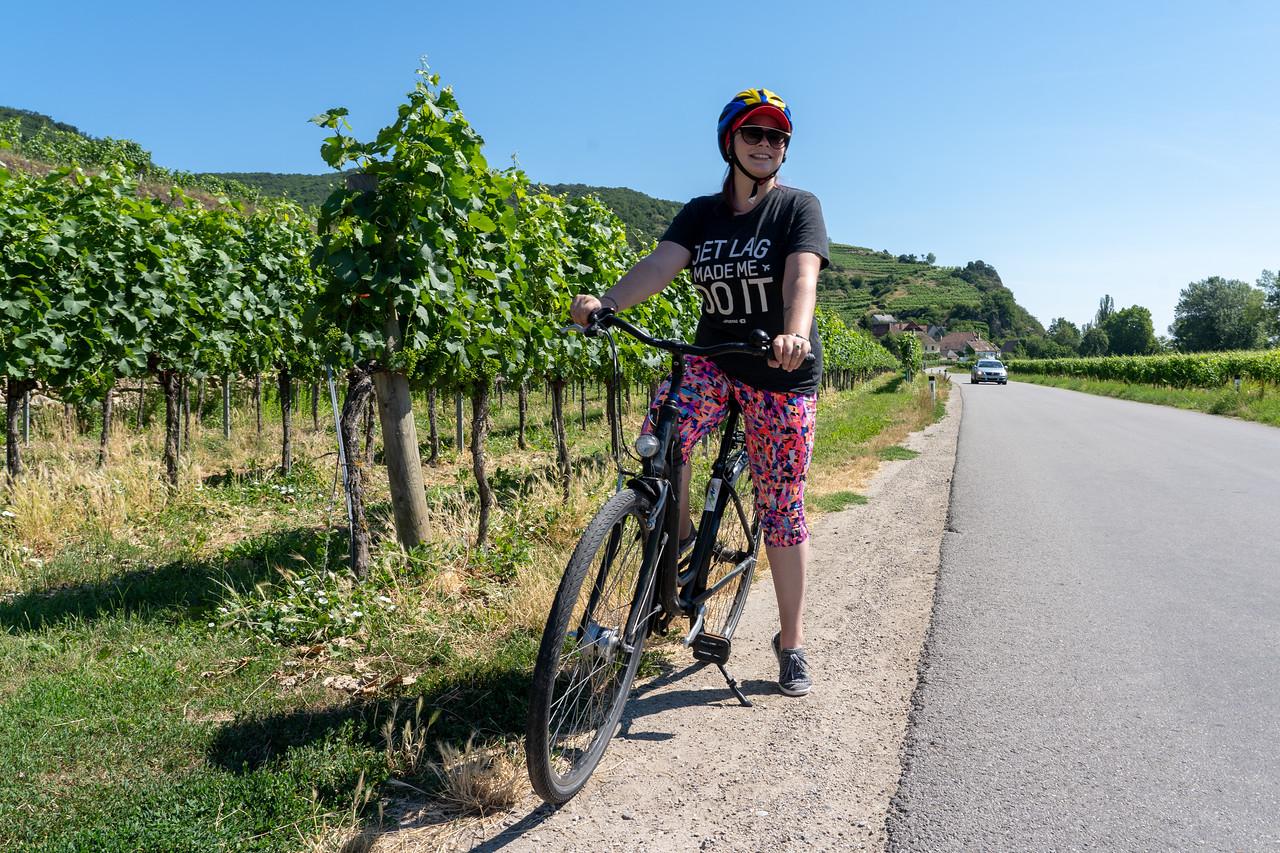 Amanda on a bike in a vineyard in Austria