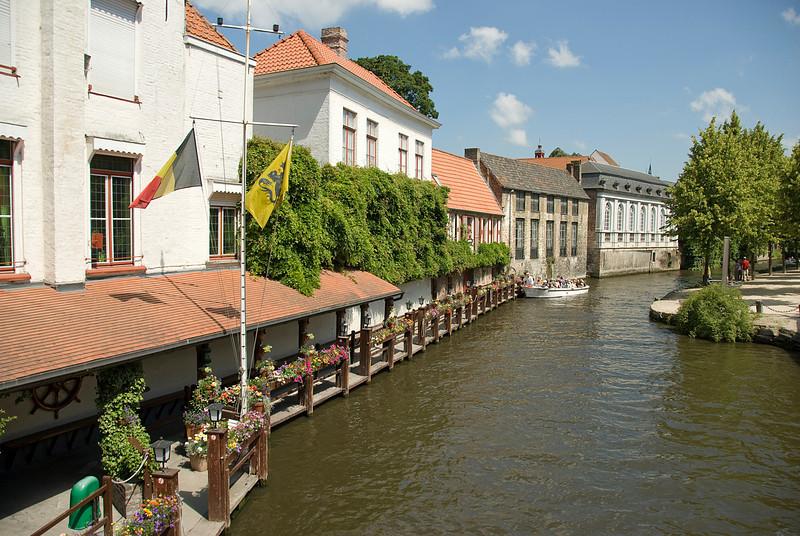 Tourist boat cruising down Dijver canal in Bruges, Belgium
