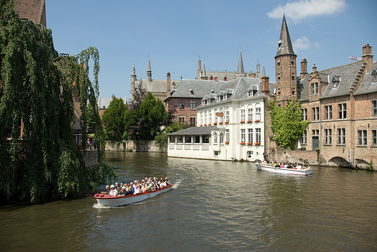 Tourists on a boat cruising the Dijver canal in Burges, Belgium