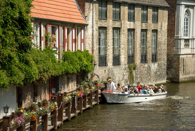 Tourists on a boat cruising the Dijver canal in Bruges, Belgium
