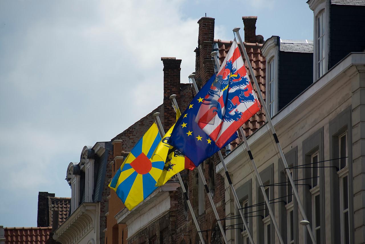 Flags waving from windows in old buildings of Bruges, Belgium