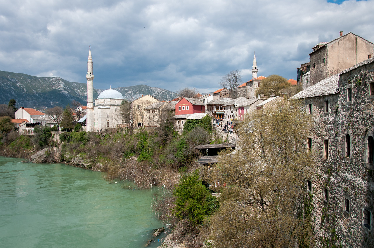 Village houses near the Hadzi Alija Mosque Tower and Neretva river in Mostar, Bosnia and Herzegovina
