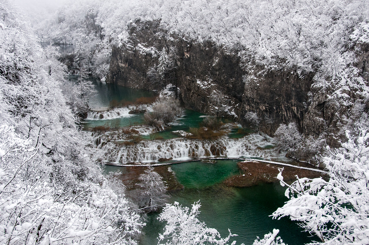 Flowing lake amidst thick snow in Plitvice National Park - Croatia