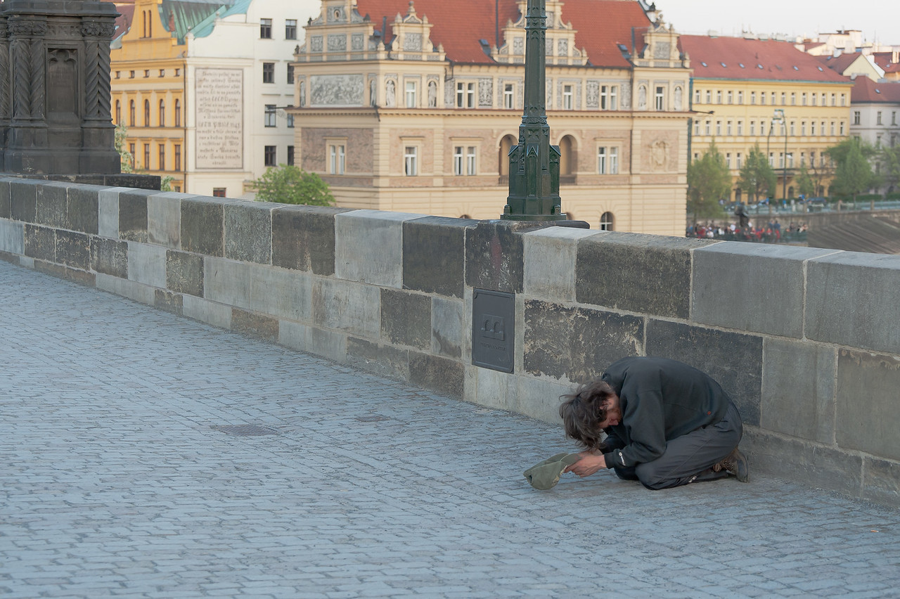 Man kneeling before a statue in Charles Bridge - Prague, Czech Republic