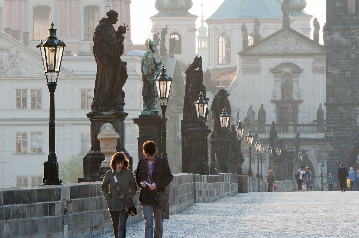 Couple walking on the Charles Bridge in Prague, Czech Republic