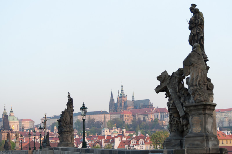 Row of statues in Charles Bridge with Prague Castle in the background - Prague, Czech Republic