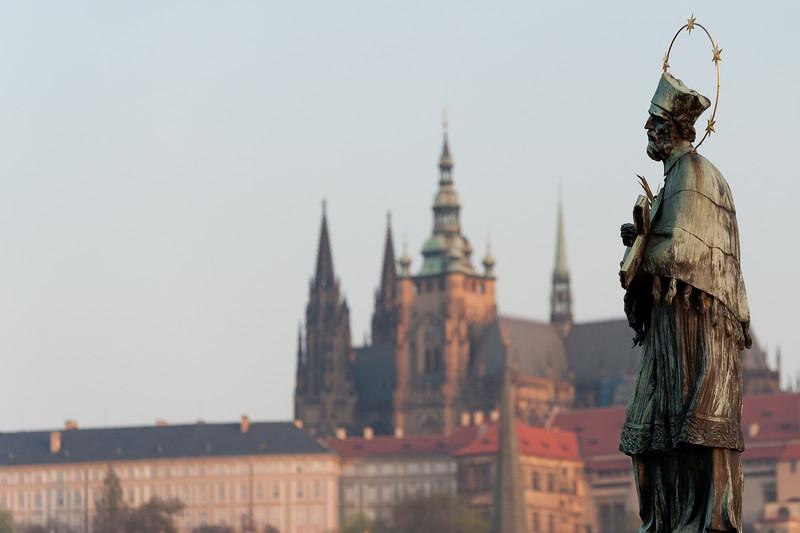 John of Nepomuk statue with Prague Castle in background - Prague, Czech Republic