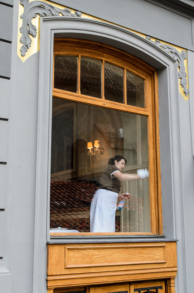 Woman cleaning window at Restaurace U Stare Synagogy.