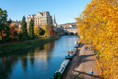 Beautiful autumn leaves and narrow boats on calm lake in Bath, England