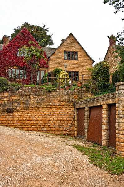 "House. Chipping Campden is a small market town within the Cotswold district of Gloucestershire, England. It is notable for its elegant terraced High Street, dating from the 14th century to the 17th century. A rich wool trading centre in the Middle Ages, Chipping Campden enjoyed the patronage of wealthy wool merchants (see also wool church). Today it is a popular Cotswold tourist destination with old inns, hotels, specialist shops and restaurants. The High Street is lined with honey-coloured limestone buildings, built from the mellow locally quarried oolitic limestone known as Cotswold stone, and boasts a wealth of fine vernacular architecture. At its centre stands the Market Hall with its splendid arches, built in 1627. Since the early seventeenth century the town has been home to a championship of rural games, which later turned into Robert Dover's Cotswold Olimpick Games. The Olimpicks are held every summer on the Friday evening following the late Spring Bank-holiday (usually late May or early June), on Dover's Hill, near Chipping Campden. Peculiar to the games is the sport of shin-kicking (hay stuffed down the trousers can ease one's brave passage to later rounds). To mark the end of the games, there is a huge bonfire and firework display. This is followed by a torch-lit procession back into the town and dancing to a local band in the square. <a href=""http://www.chippingcampden.co.uk/"">http://www.chippingcampden.co.uk/</a> ."