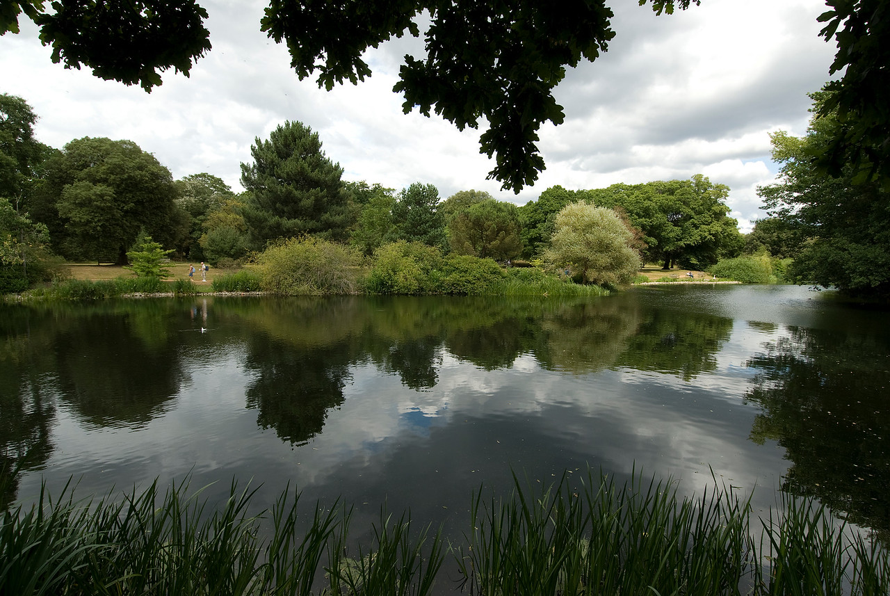 Calm lake and greens at the Royal Botanical Gardens in Kew, England
