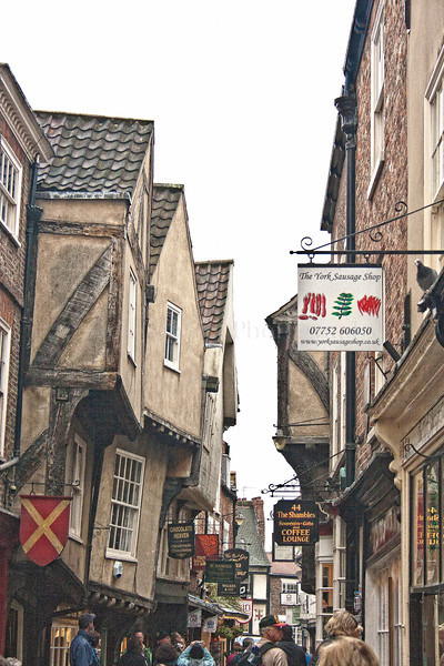 "The Shambles. The ancient street of the Butchers of York, mentioned in the Domesday Book of William the Conqueror.  It takes its name from the word 'Shamel' meaning the stalls or benches on which the meat was displayed - later versions of which can still be seen.  It was rebuilt about 1400 when it assumed its present character. York is a walled city, situated at the confluence of the Rivers Ouse and Foss in North Yorkshire, England. The city has a rich heritage and has provided the backdrop to major political events throughout much of its two millennia of existence. The city was founded by the Romans in 71 AD. They called it Eboracum, a name perhaps derived from one used by the British tribes who inhabited the area. The Romans made it the capital of their Province of Britannia Inferior.[4] At the end of Roman rule in 415 AD the settlement was taken over by the Angles and the city became known as Eoforwic. The city came to be the episcopal, and later, royal centre of the Kingdom of Northumbria.[5] The Vikings captured the city in 866 AD, and for the period between 866 and the final incorporation of Northumbria into the Kingdom of England in 954, York is sometimes referred to by modern writers by its Scandinavianised form, Jórvík. The name in its modern form ""York"" was first used in the 13th century. Renowned for its Roman, Viking, and Medieval heritage and wealth of attractions like and the iconic York Minster and JORVIK York is fast developing a flourishing cutting edge scene.   Broaden your mind with a visit to world class museums like the National Railway Museum and with a host of magnificent events, entertaining guided walks and boat trips on the River Ouse, there is something to keep you entertained throughout your stay.   Delve into the city's vibrant café culture or simply watch the world go by while sipping a drink at a riverside stylish bar or in one of the many cities' heritage taverns. <a href=""http://www.visityork.org/"">http://www.visityork.org/</a> ."