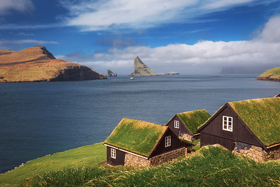 Village of Bour on Faroe Islands with Drangarnir sea stack in the background