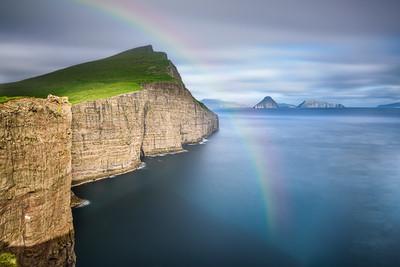 Giant sea cliffs on Faroe Islands with a rainbow