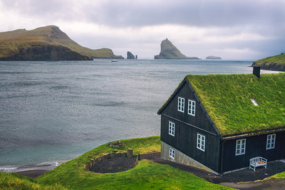 House on the coast of Faroe Islands with Drangarnir sea stack in the background