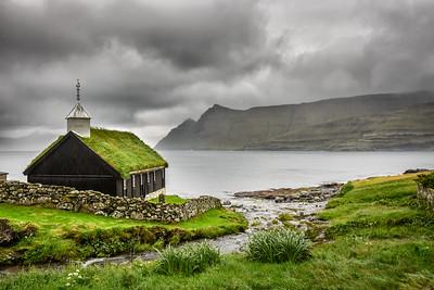 Small village church under heavy clouds