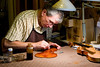 Guy Tinel at work repairing the finish on a violin he made in 1991.