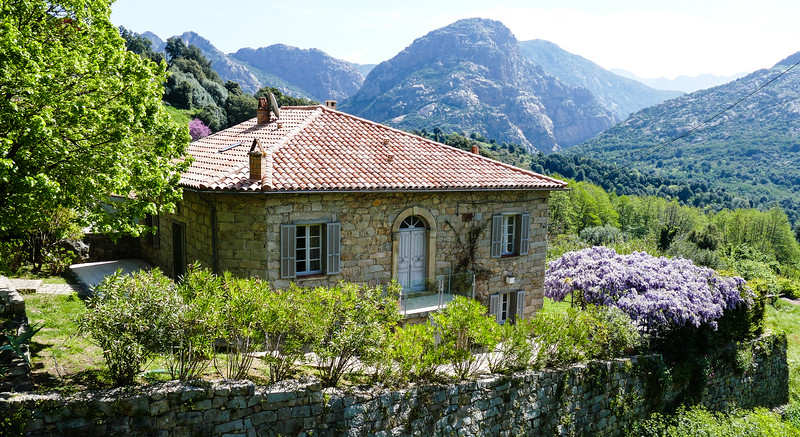 Stone house with red tile roof sits in a valley in Corsica surrounded by mountains and greenery.