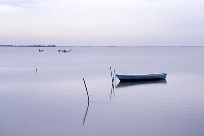 A lone fishing boat anchored to a pole on the still morning waters of the Camargue
