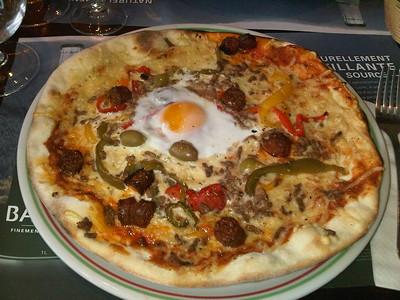 "Orientale Pizza - tomato sause, cheese, olives, merguez sausage, minced meat, egg & peppers. €10. Served in ""Brasserie Le Tramway"" in Lyon  09/06/14"