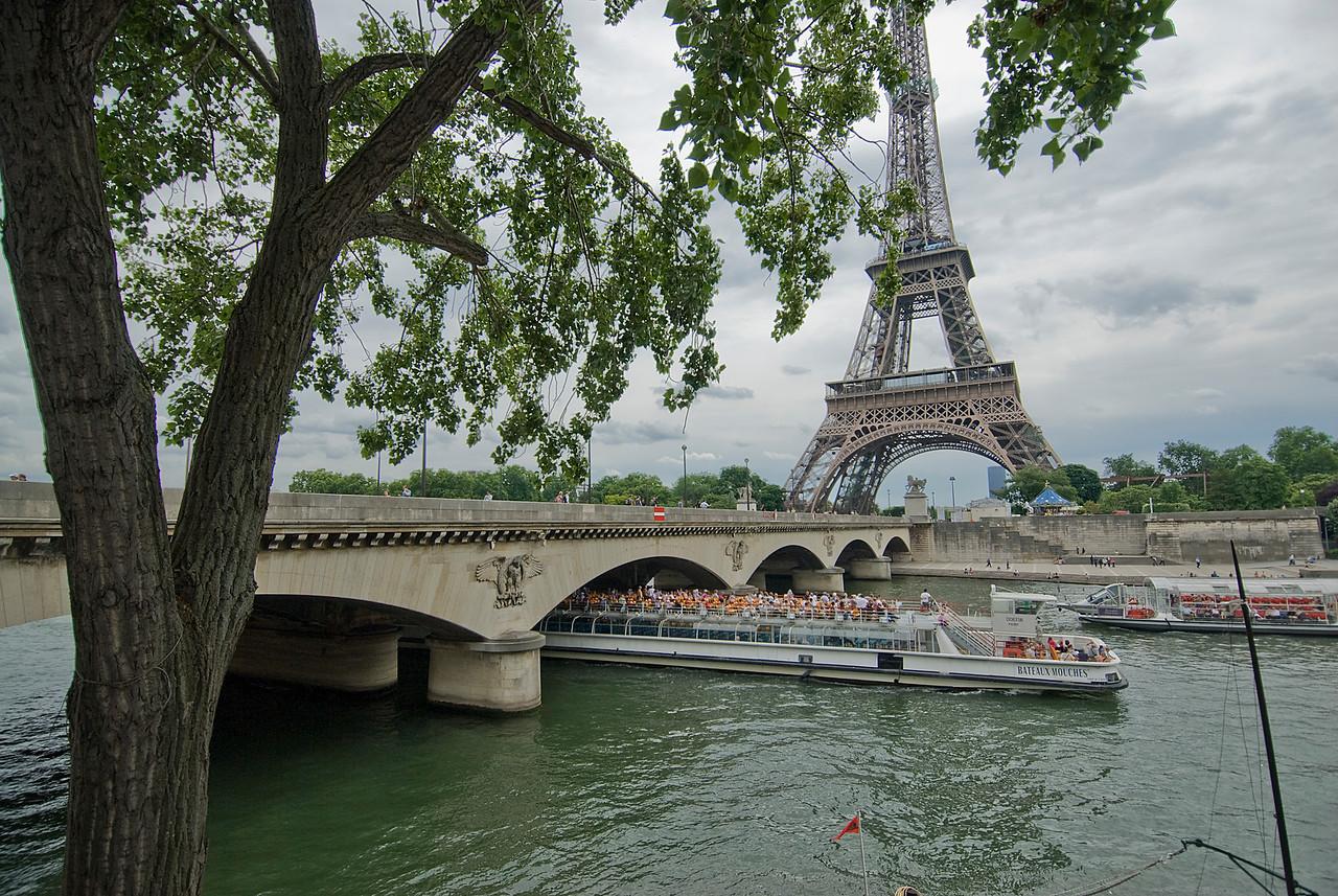Tourist boat cruising below Eiffel Tower Bridge - Paris, France
