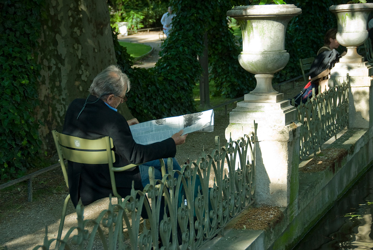 Man reading the newspaper in a park - Paris, France