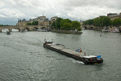 Boat cruising down river near Pont Neuf in Paris, France