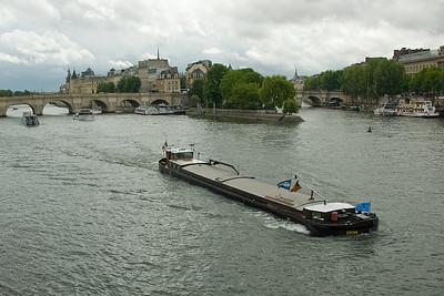 Boat cruising down river near Pont Neuf in Paris, France