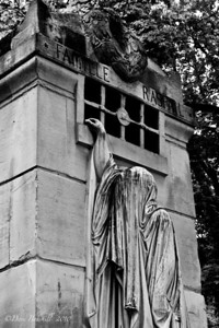 The Grim Reaper guards a grave at Pere-La-Chaise Cemetery in Paris, France