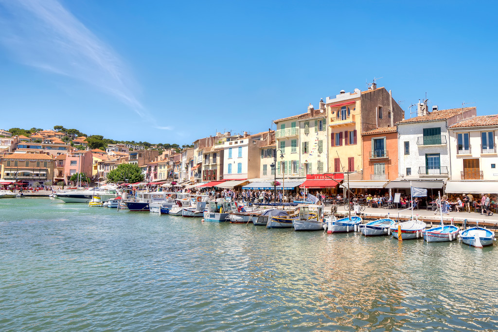 cassis water showing harbour with boats and buildings with blue sky
