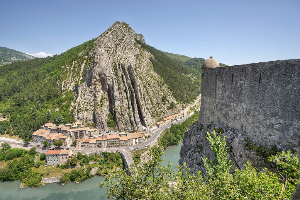 view of the sisteron devil's sentry with the river mountain and village in the background