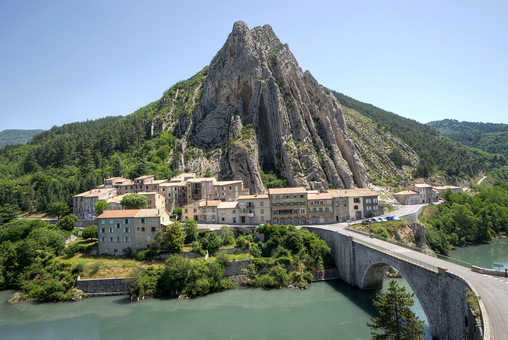 view across the duran river from sisteron of small town and triangular mountain peak