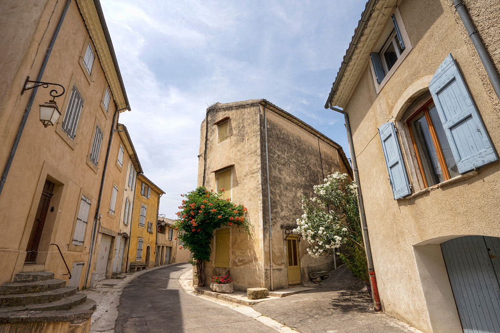 intersection in lourmarin, bare walls powder blue shutters and doors
