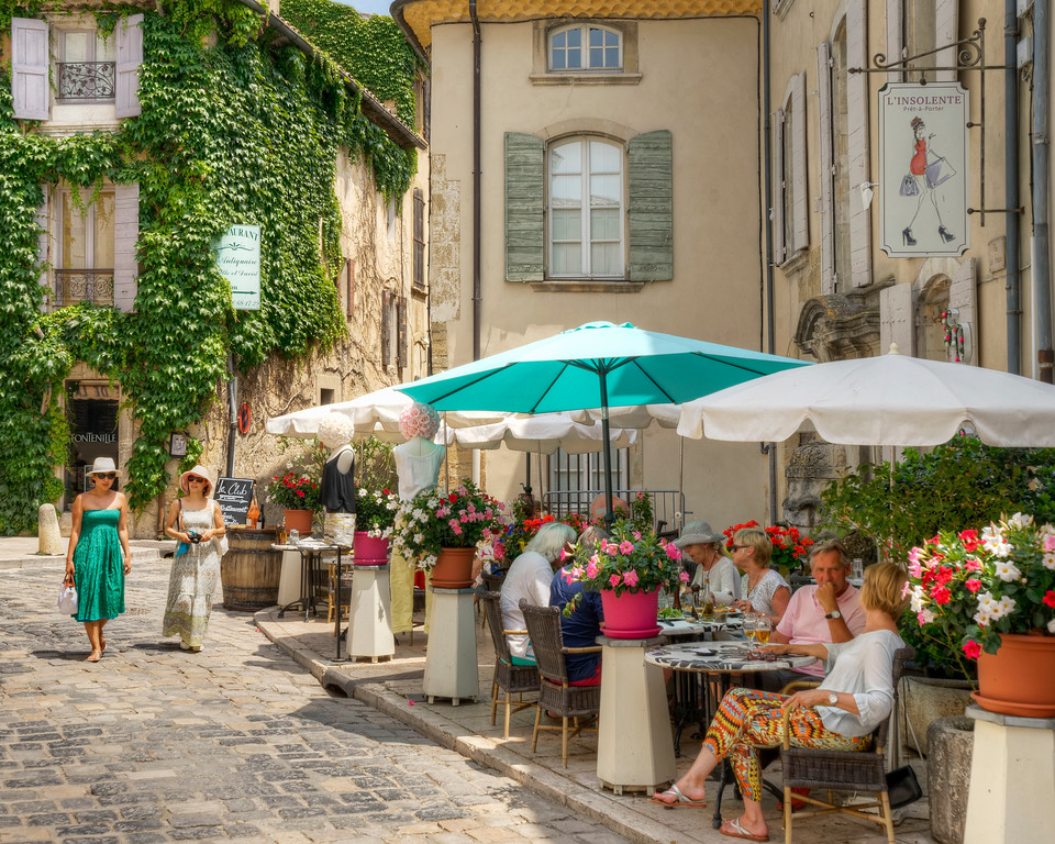 friends strolling through lourmain provence france main street while couples dine and relax at streetside cafes