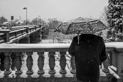 Rear view of man with umbrella in snowy Frankfurt