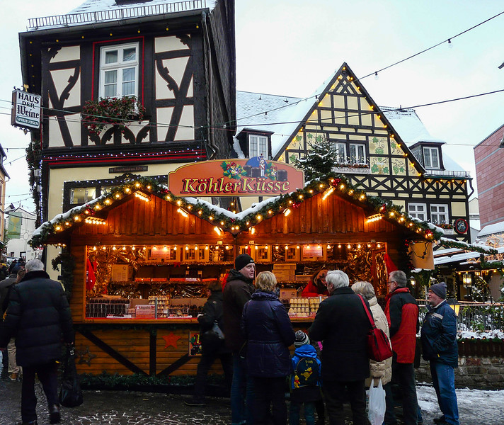 People standing in front of a Christmas market stand