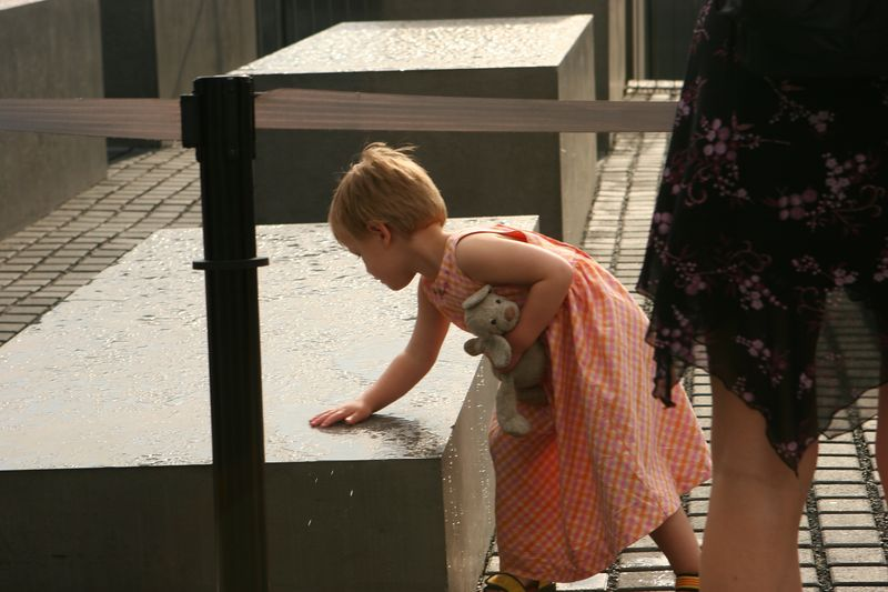 Young girl visiting the Berlin Jewish memorial, wiping away the puddled rain.